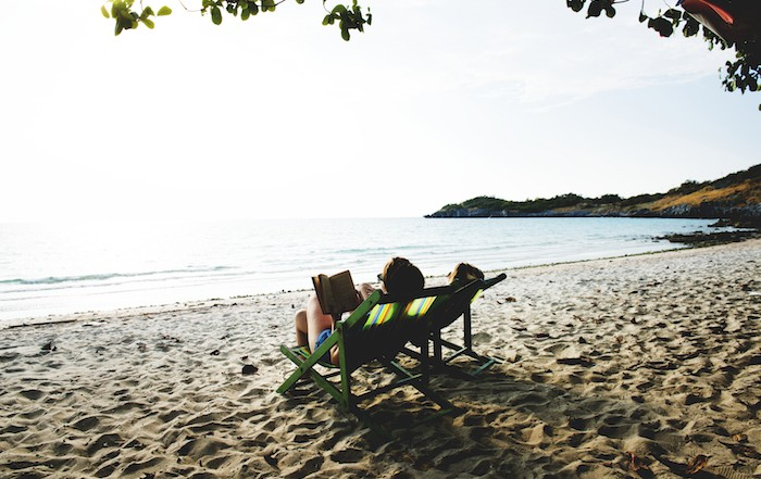 Retired person relaxing on a deckchair, reading a book on a beach paradise
