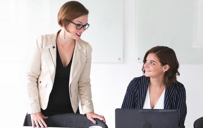 Two women in smart casual business attire talking to each other. One of the women is sitting at a laptop, the other offering advice