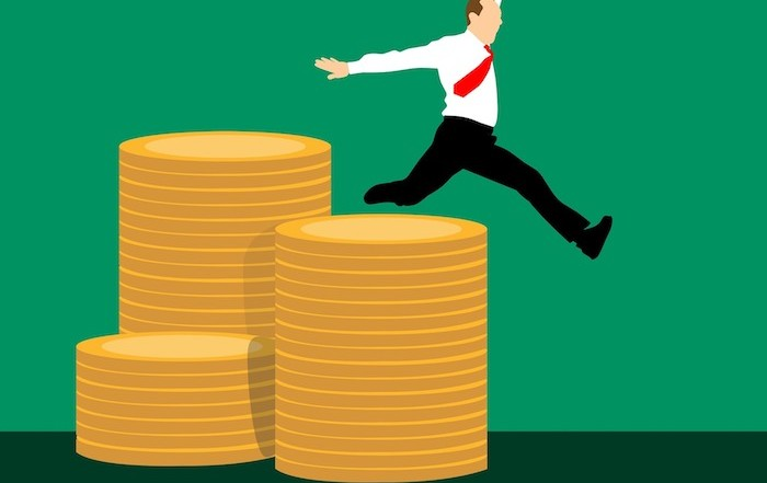 Joyful savings - illustration of a businessman leaping off stacks of coins
