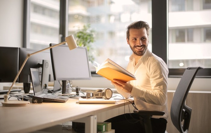 Smiling business man holding a workbook in front of a computer on a desk