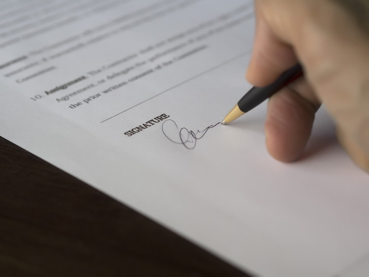 Contractor's hand holding a pen and signing a contract