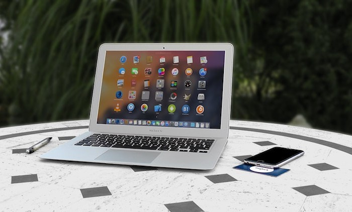 Laptop and phone on a table displaying a full range of apps