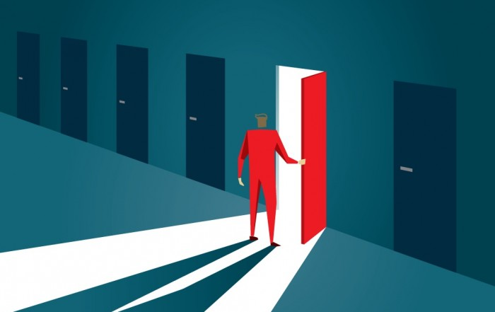 A silhouette figure opens a red door in a dark room to a bright new opportunity.