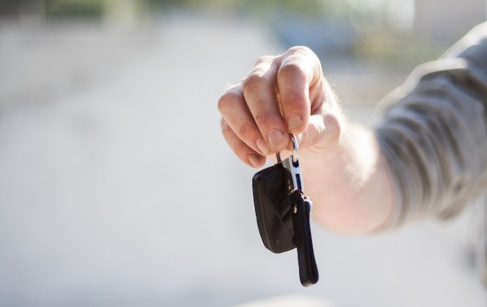 Hand holding a set of car keys, giving it to you