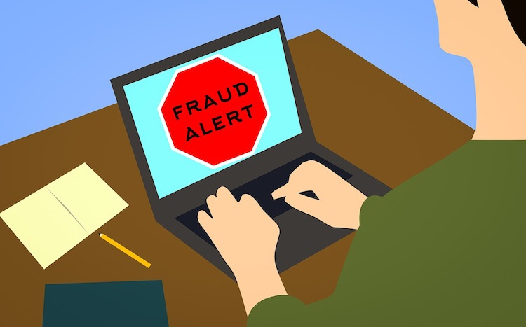 Spotting a fraud or scam with a sign on a computer reading 'fraud alert'