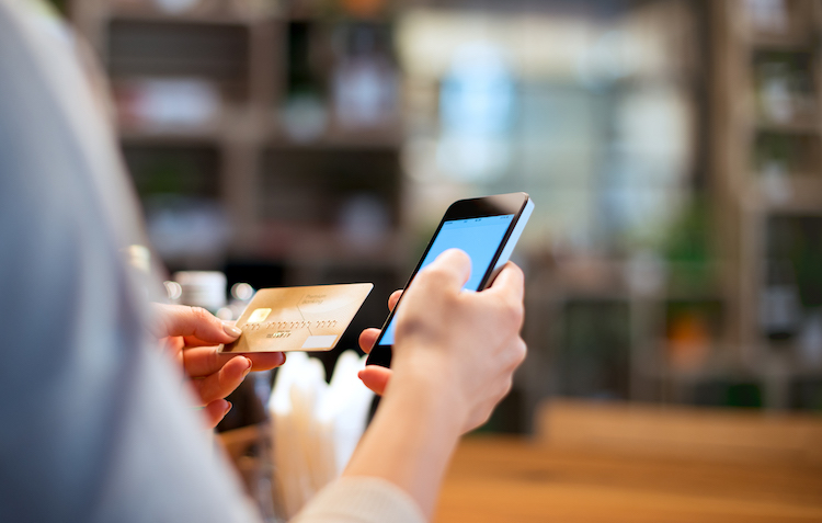 Woman is banking online with mobile phone. She use credit card and the smartphone.
