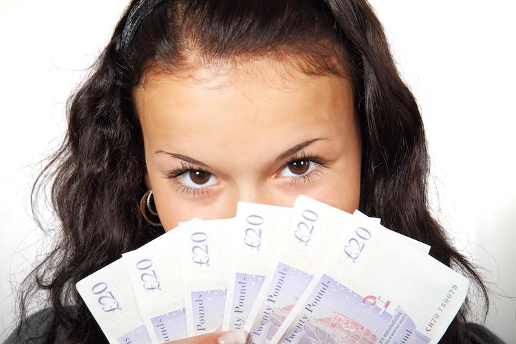 Female contractor holding six £20 notes in front of her face