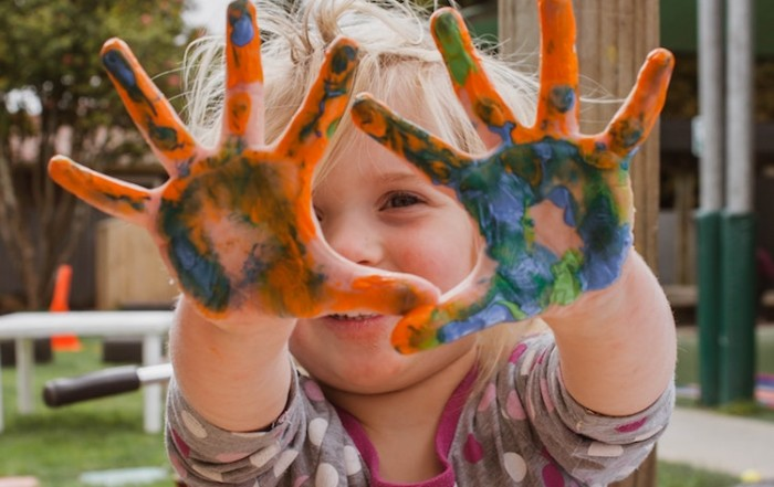 Child at childcare with paint on hands.