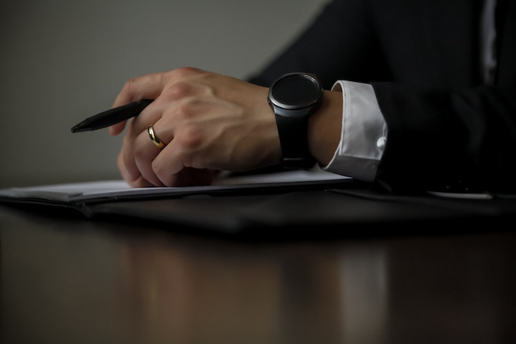 Man holding a pen in a suit.