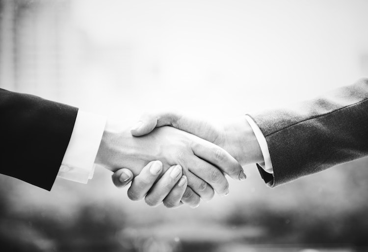 Hands shaking in black and white, agreeing a business loan.
