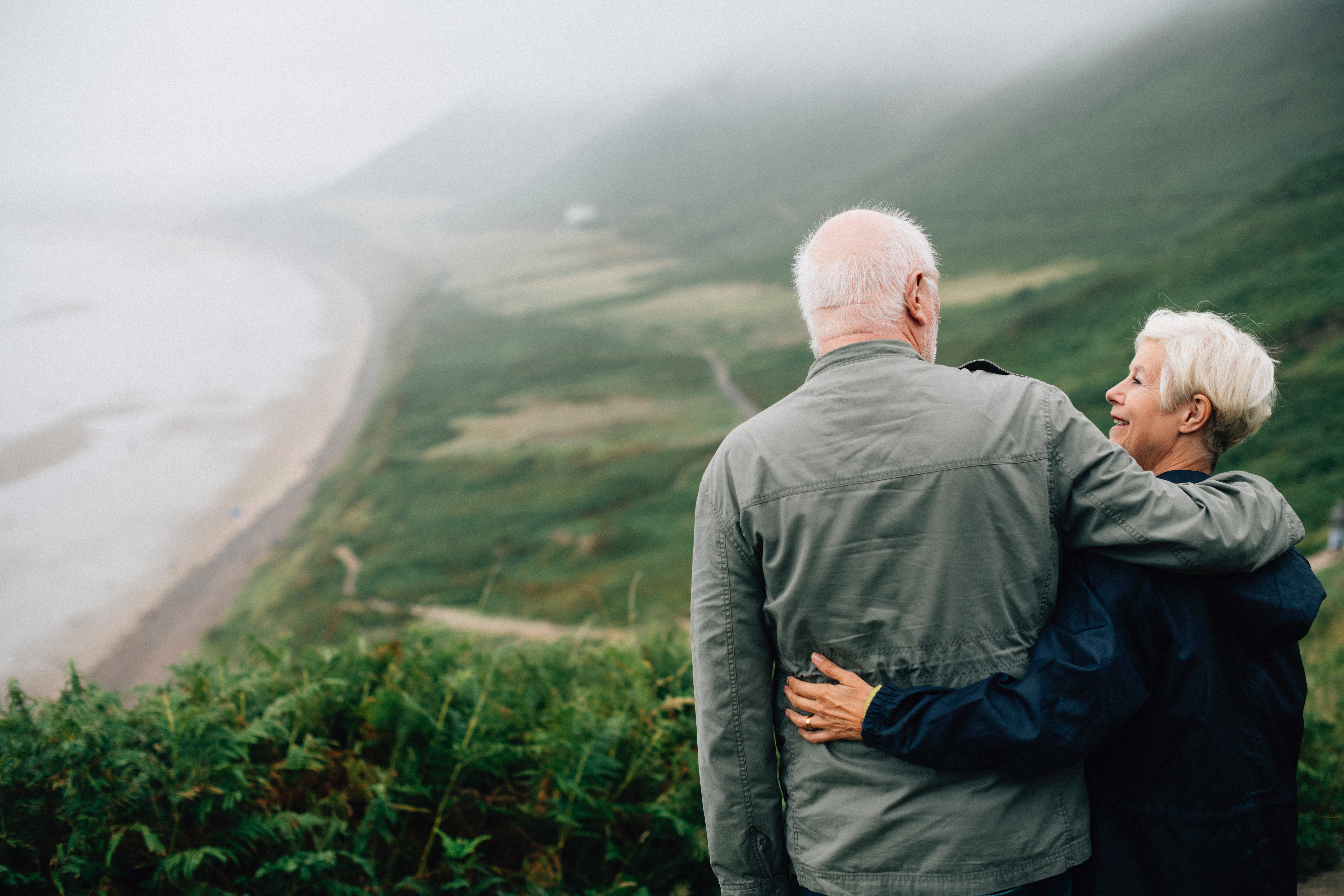Retired couple, looking over the sea.