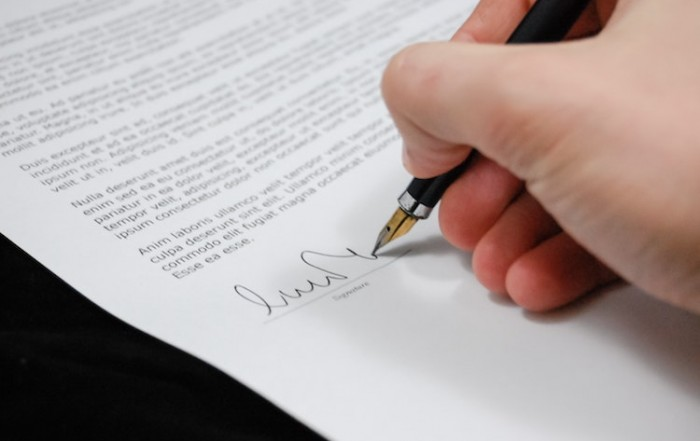Hand signing a will.