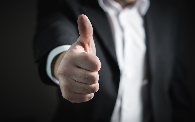 man in suit with thumbs up.