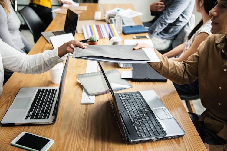 Person handing over CV on desk.