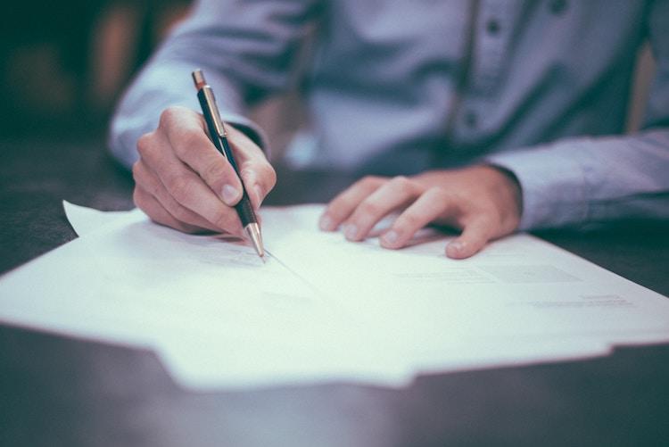 Man signing directors loans agreement.